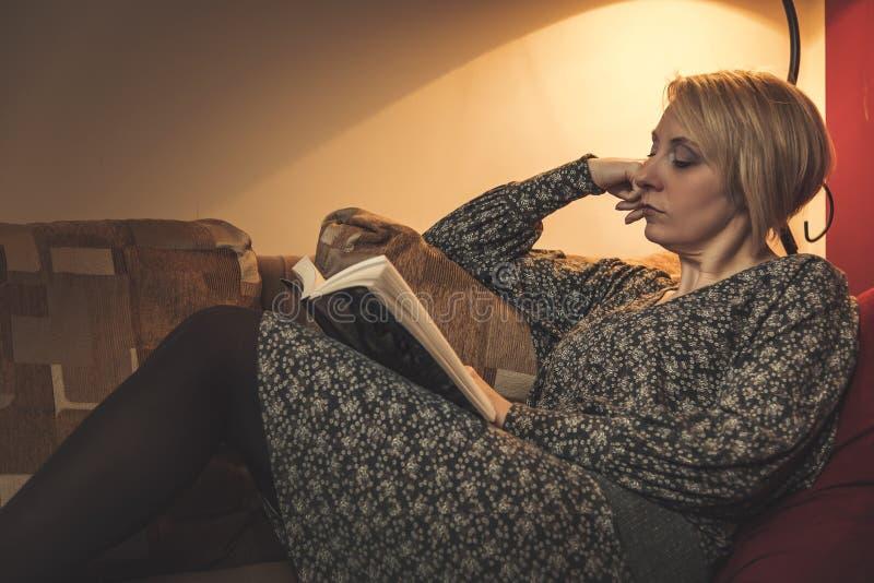 Το ενδιαφέρον βιβλίο μια ώριμη γυναίκα διαβάζει στοκ φωτογραφίες