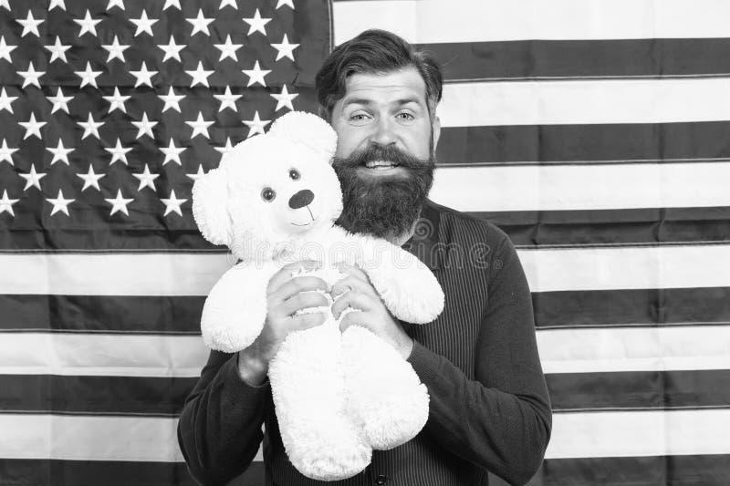 Το ενθουσιώδες πνεύμα Πατριώτης που κρατά αρκουδάκι την ημέρα της ανεξαρτησίας Ο γενειοφόρος χίπστερ είναι πατριωτικός για τις ΗΠ στοκ εικόνες