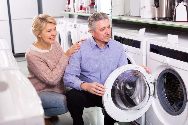 Το ενδιαφερόμενο ώριμο ζεύγος επιλέγει το πλυντήριο για το σπίτι τους στοκ φωτογραφία με δικαίωμα ελεύθερης χρήσης