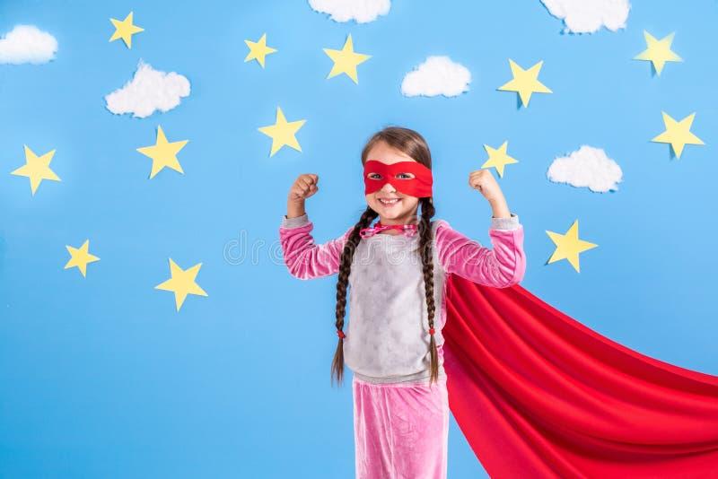 Το εξαετές ξανθό κορίτσι έντυσε όπως το superhero έχοντας τη διασκέδαση στο σπίτι Παιδί στο υπόβαθρο του φωτεινού μπλε τοίχου στοκ εικόνα