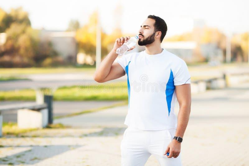 Το εξαντλημένο άτομο δρομέων πίνει το νερό στο πάρκο μετά από το workout στοκ εικόνες