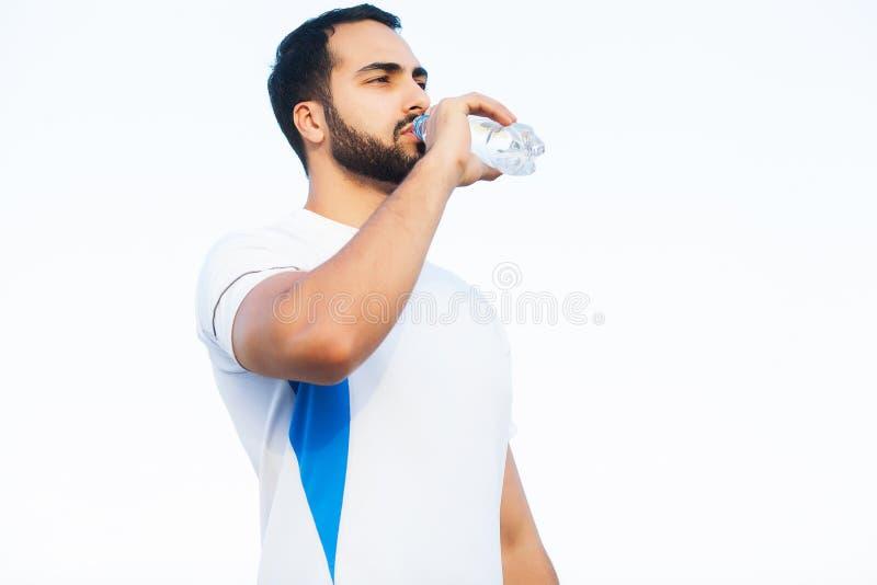 Το εξαντλημένο άτομο δρομέων πίνει το νερό στο πάρκο μετά από το workout στοκ φωτογραφία με δικαίωμα ελεύθερης χρήσης