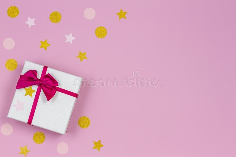 Το εορταστικό κιβώτιο δώρων με το τόξο σατέν και ακτινοβολεί σπινθηρίσματα κομφετί στο ελαφρύ ρόδινο υπόβαθρο κρητιδογραφιών r στοκ φωτογραφίες