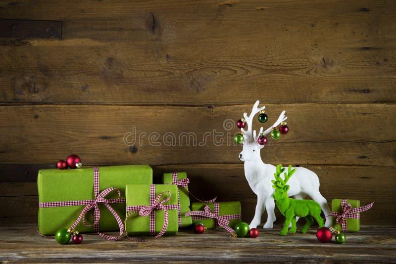 Το εορταστικό υπόβαθρο Χριστουγέννων με παρουσιάζει και τάρανδος στο κόκκινο α στοκ φωτογραφία με δικαίωμα ελεύθερης χρήσης