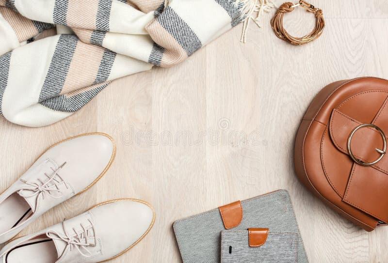 Το επίπεδο γυναικών ` s βάζει τα παπούτσια ενδυμάτων, μαντίλι, βραχιόλι, τσάντα, ταμπλέτα, sm στοκ εικόνες