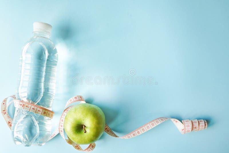 Το επίπεδο διατροφής βάζει την κορδέλλα ενός μέτρου και το πράσινο μήλο και ένα μπουκάλι νερό μπλε υπόβαθρο με το διάστημα αντιγρ στοκ εικόνα