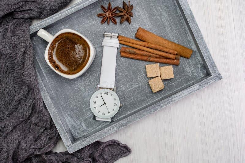 Το επίπεδο προγευμάτων βρέθηκε Wristwatch, φλιτζάνι του καφέ, αστέρια γλυκάνισου, ραβδιά κανέλας σε έναν δίσκο r Δημιουργική έννο στοκ φωτογραφίες