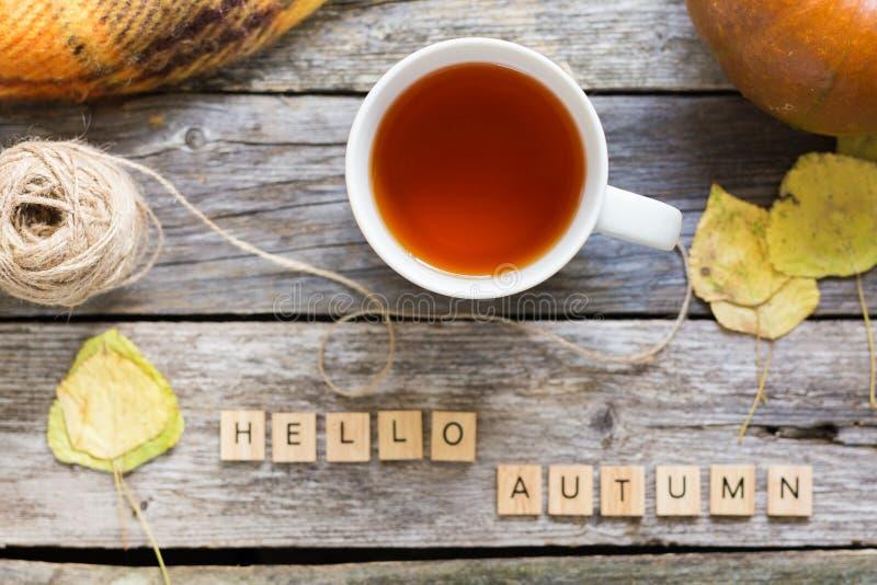Το επίπεδο πτώσης φθινοπώρου βάζει, τοπ άποψη Φύλλα πτώσης, κούπα του τσαγιού κολοκύθα με το φθινόπωρο επιγραφής γειά σου αγροτικ στοκ εικόνες