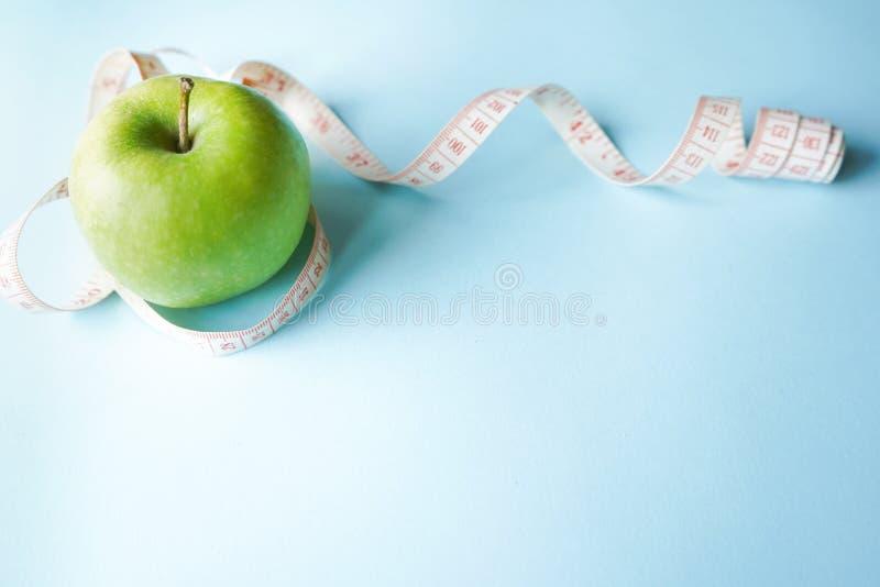Το επίπεδο συμβόλων διατροφής βάζει την κορδέλλα ενός μέτρου και το πράσινο μήλο μπλε υπόβαθρο με το διάστημα αντιγράφων έννοια υ στοκ εικόνες