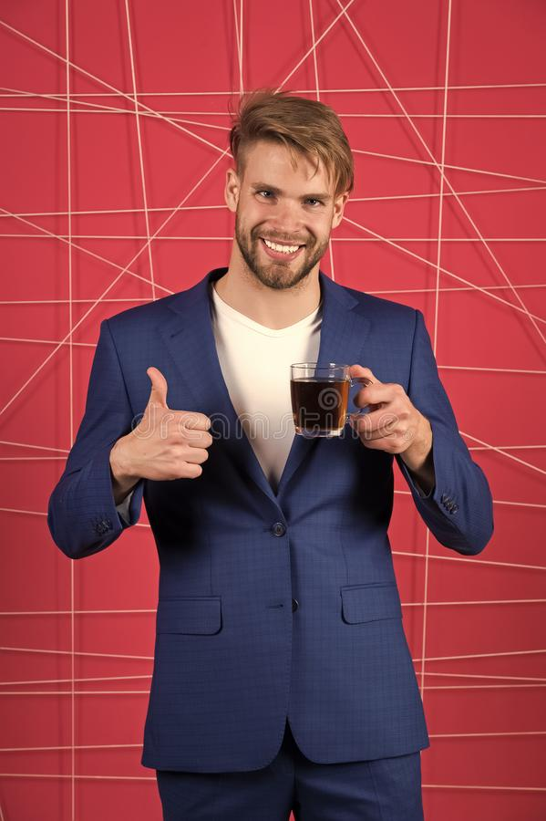 Το επίσημο κομψό κοστούμι ατόμων παρουσιάζει αντίχειρα επάνω στη χειρονομία Ο κομψός τύπος αγάμων πίνει το τσάι ή τον καφέ και συ στοκ φωτογραφία