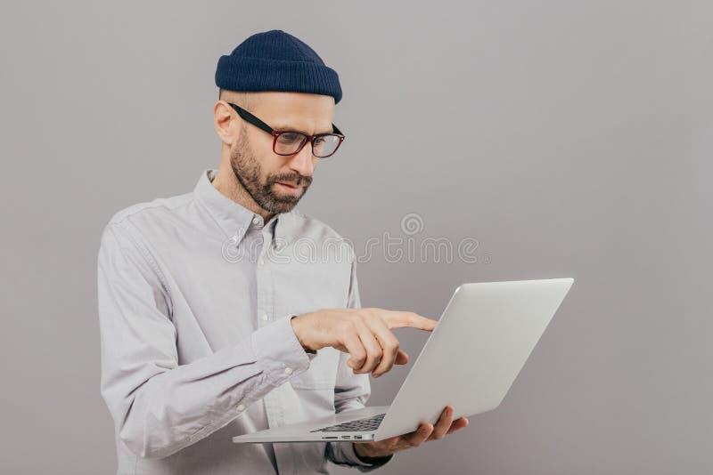 Το επαγγελματικό αρσενικό freelancer κάνει την εργασία προγράμματος, δείχνει με το αντίχειρα στην οθόνη του φορητού προσωπικού υπ στοκ εικόνα με δικαίωμα ελεύθερης χρήσης