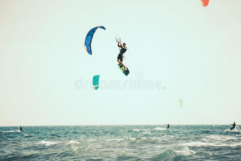 Το επαγγελματικό kiter κάνει το δύσκολο τέχνασμα σε ένα όμορφο υπόβαθρο στοκ φωτογραφία