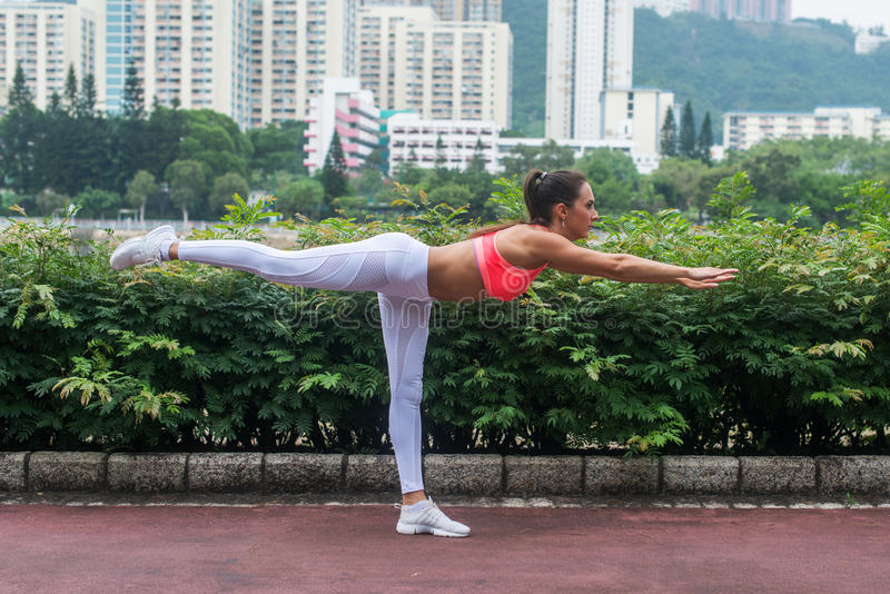 Το επαγγελματικό θηλυκό οριζόντιο ισορροπώντας ραβδί γιόγκας άσκησης αθλητών θέτει τη στάση σε ένα πόδι που κρατά την ισορροπία μ στοκ φωτογραφία με δικαίωμα ελεύθερης χρήσης