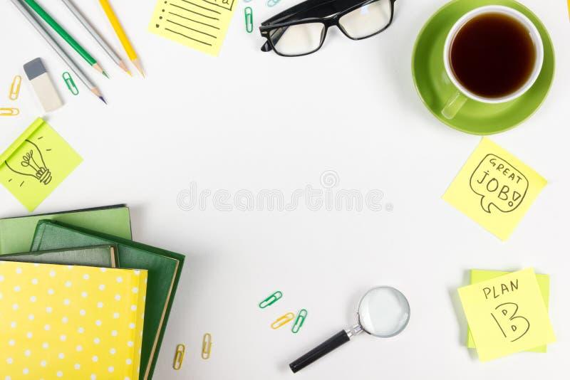 Το επιτραπέζιο γραφείο γραφείων με τις πράσινες προμήθειες, κενό σημειωματάριο, φλυτζάνι, μάνδρα, γυαλιά, τσαλάκωσε το έγγραφο, ε στοκ εικόνες