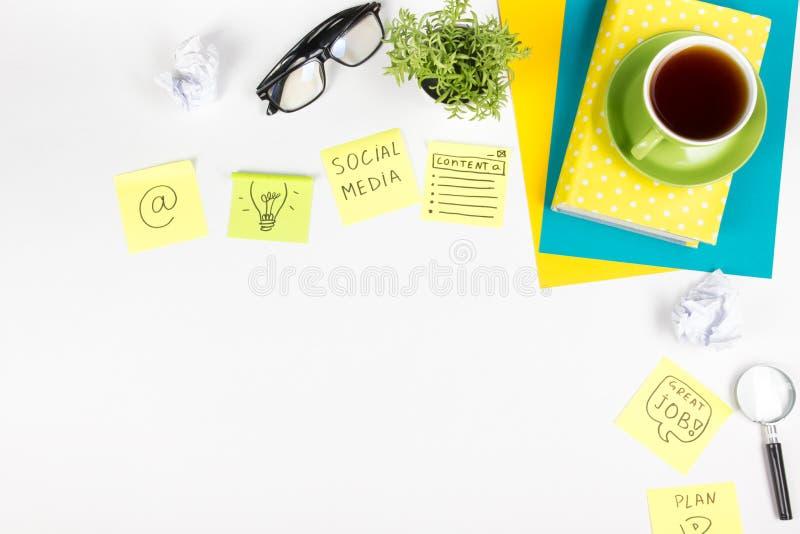 Το επιτραπέζιο γραφείο γραφείων με τις πράσινες προμήθειες, κενό σημειωματάριο, φλυτζάνι, μάνδρα, γυαλιά, τσαλάκωσε το έγγραφο, ε στοκ φωτογραφίες