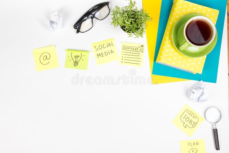 Το επιτραπέζιο γραφείο γραφείων με τις πράσινες προμήθειες, κενό σημειωματάριο, φλυτζάνι, μάνδρα, γυαλιά, τσαλάκωσε το έγγραφο, ε στοκ φωτογραφία