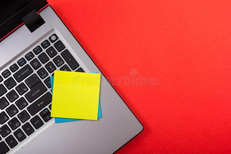 Το επιτραπέζιο γραφείο γραφείων με το σύνολο ζωηρόχρωμων προμηθειών, άσπρο κενό σημειωματάριο, φλυτζάνι, μάνδρα, PC, τσαλάκωσε το στοκ φωτογραφία