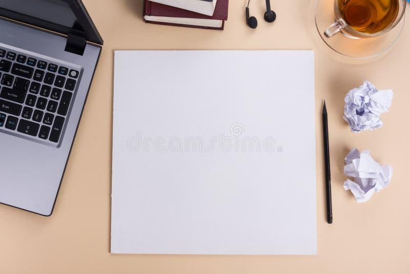 Το επιτραπέζιο γραφείο γραφείων με το σύνολο ζωηρόχρωμων προμηθειών, άσπρο κενό σημειωματάριο, φλυτζάνι, μάνδρα, PC, τσαλάκωσε το στοκ εικόνα