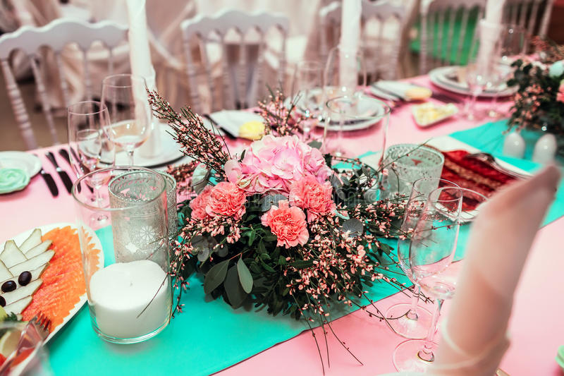 Το επιτραπέζιο ντεκόρ με τα λουλούδια παρουσιάζει τους αριθμούς και τα κεριά Διακόσμηση γαμήλιου συμποσίου στοκ εικόνα με δικαίωμα ελεύθερης χρήσης