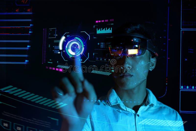Το επιχειρησιακό άτομο δοκιμάζει vr τα γυαλιά hololens στο σκοτεινό δωμάτιο | Νέα ασιατική εμπειρία AR αγοριών με τη γήινη σφαίρα στοκ φωτογραφία