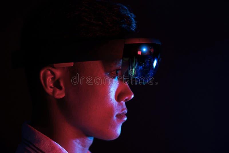 Το επιχειρησιακό άτομο δοκιμάζει vr τα γυαλιά hololens στο σκοτεινό δωμάτιο | Νέα ασιατική εμπειρία AR αγοριών με τη γήινη σφαίρα στοκ φωτογραφίες με δικαίωμα ελεύθερης χρήσης