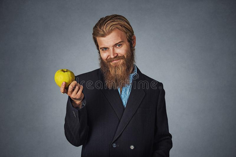 Το επιχειρησιακό άτομο κρατά ένα πράσινο μήλο και χαμογελά στοκ εικόνες