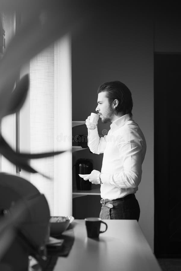 Το επιχειρησιακό άτομο πίνει έναν καφέ, γραφείο στοκ φωτογραφία