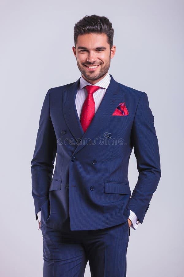 Download Το επιχειρησιακό άτομο που χαμογελά και που θέτει με παραδίδει τις τσέπες Στοκ Εικόνα - εικόνα από στούντιο, μοντέλο: 62722173