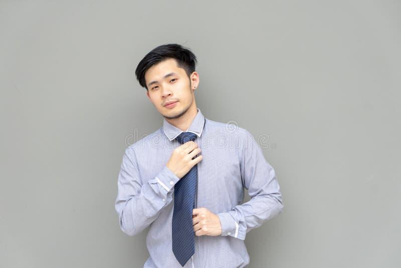 Το επιχειρησιακό άτομο στο πουκάμισο ρυθμίζει το δεσμό Νέο ασιατικό άτομο πορτρέτου που ρυθμίζει τη γραβάτα του στεμένος στο γκρί στοκ εικόνα