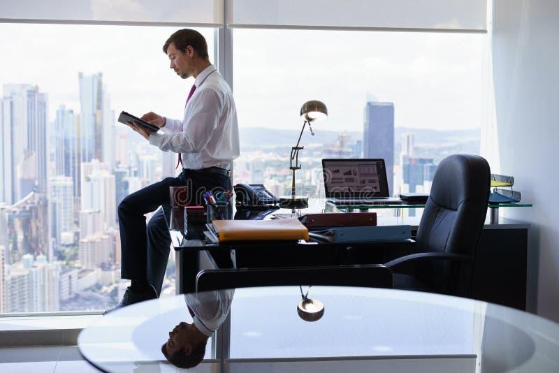 Το επιχειρησιακό πρόσωπο διαβάζει τις ειδήσεις στο PC ταμπλετών το πρωί στοκ εικόνες με δικαίωμα ελεύθερης χρήσης