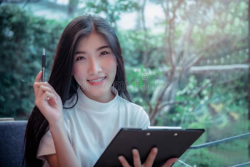 Το επιχειρησιακό ύφος του ασιατικού κοριτσιού κρατά ένα θετικό πράγμα συγκίνησης μανδρών και χαμόγελου της ημέρας στοκ εικόνα