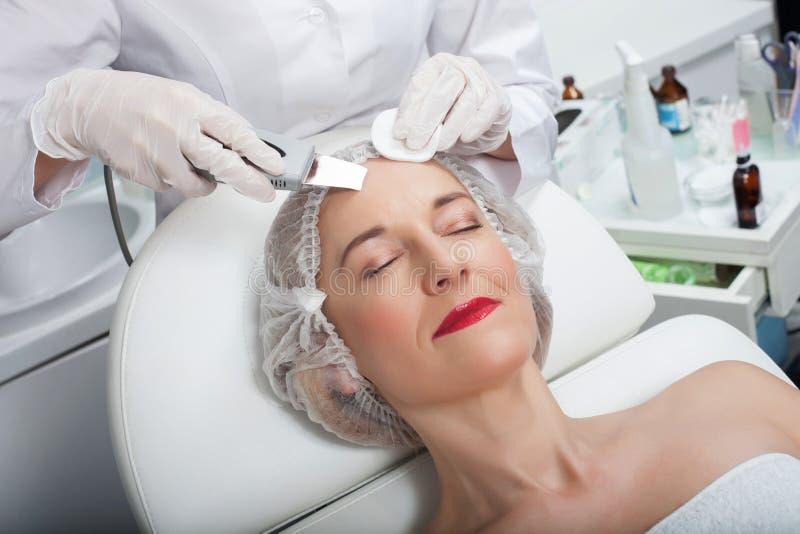 Το επιδέξιο θηλυκό beautician υποβάλλεται στην επεξεργασία λέιζερ στοκ φωτογραφία