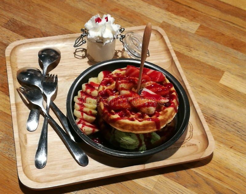 Το επιδόρπιο βαφλών, καυτό κέικ βαφλών επάνω από την πράσινη εξυπηρέτηση παγωτού τσαγιού με κτυπά την κρέμα και το φρέσκο κάλυμμα στοκ εικόνα