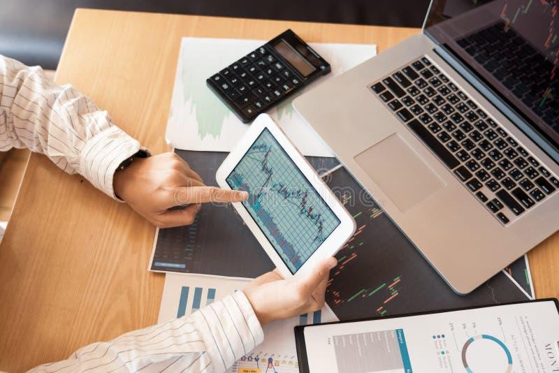 Το εργαζόμενο επιχειρησιακό άτομο του μεσίτη ή οι έμποροι που σκέφτονται για τα Forex στις πολλαπλάσιες οθόνες υπολογιστή του χρη στοκ φωτογραφίες