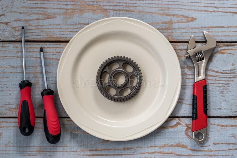 Το εργαλείο βρίσκεται σε ένα πιάτο σε έναν ξύλινο πίνακα στοκ φωτογραφίες