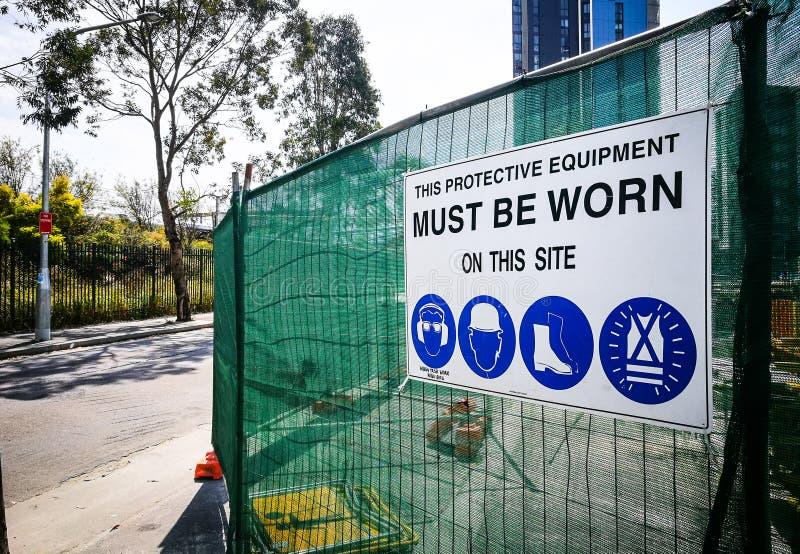 Το εργοτάξιο οικοδομής προειδοποιητικών σημαδιών για πρέπει να φορεθεί αυτόν τον προστατευτικό εξοπλισμό σε αυτήν την περιοχή στοκ εικόνες