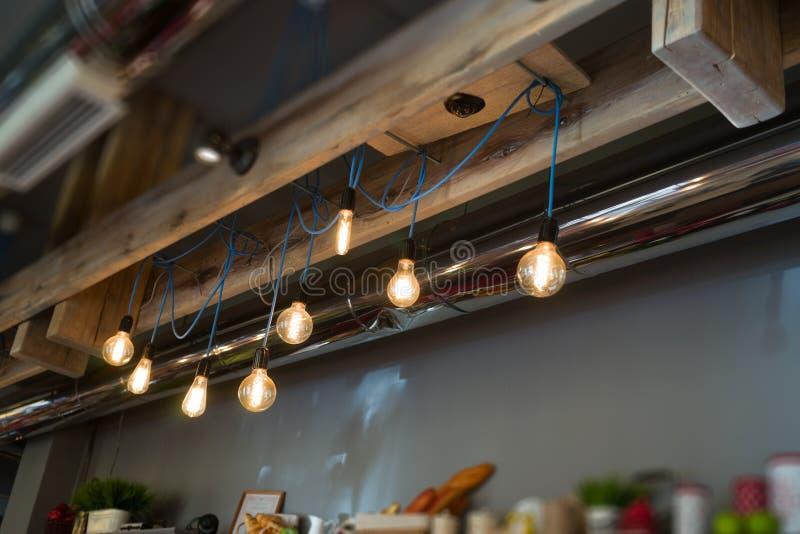 Το εσωτερικό είναι σοφίτα-ύφος με τους φωτεινούς λαμπτήρες του Edison στα μακριά σκοινιά στοκ εικόνα