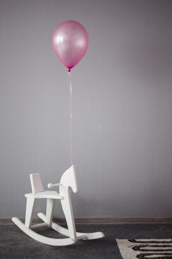 το εσωτερικό του δωματίου των παιδιών, ενός αλόγου παιχνιδιών και ενός ρόδινου μπαλονιού διακοσμημένο δωμάτιο των παιδιών στοκ εικόνα