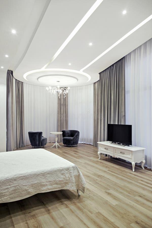 Το εσωτερικό του εξοχικού σπιτιού: μια κρεβατοκάμαρα με ένα μεγάλο άσπρο κρεβάτι στοκ φωτογραφίες