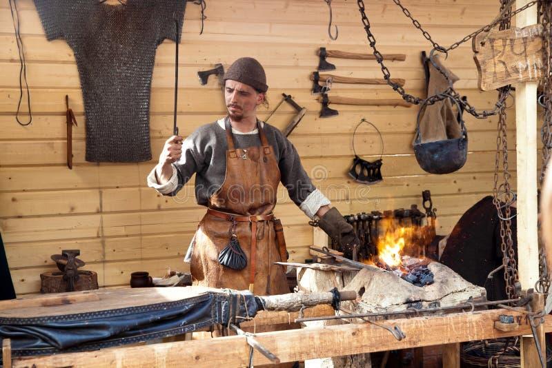 Το ετήσιο φεστιβάλ σε Kolomenskoye Αναδημιουργία αρχαίο Rus Ο σιδηρουργός φυσά τους φυσητήρες στοκ εικόνα