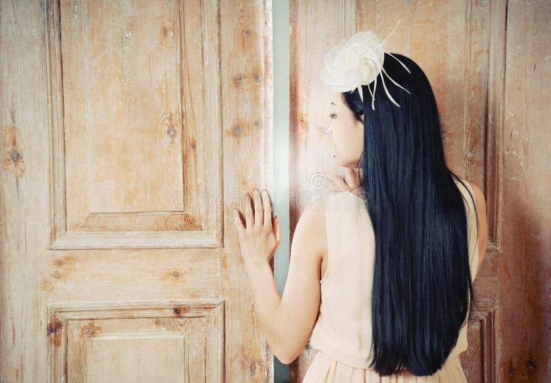 Το ευγενές όμορφο brinette ανοίγει την πόρτα στο μαγικό κόσμο στοκ φωτογραφία με δικαίωμα ελεύθερης χρήσης