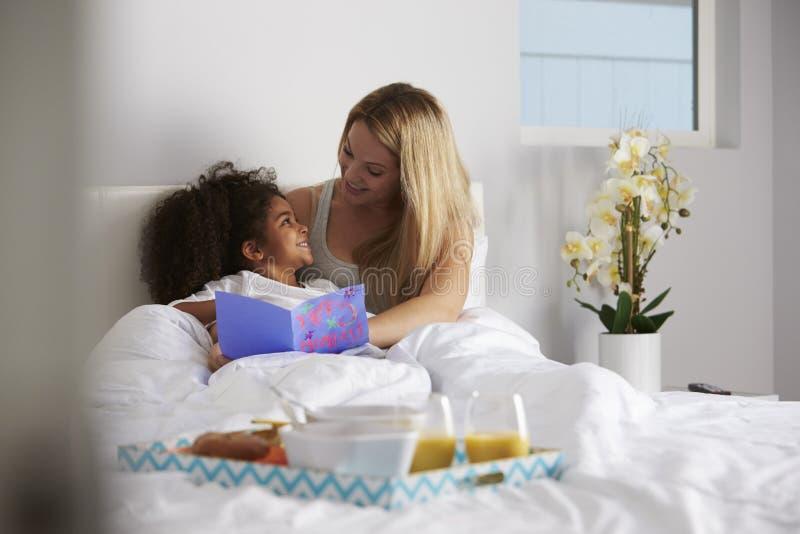 Το λευκό mum και η μαύρη κόρη εξετάζουν το ένα το άλλο, πλήρες μήκος στοκ εικόνα