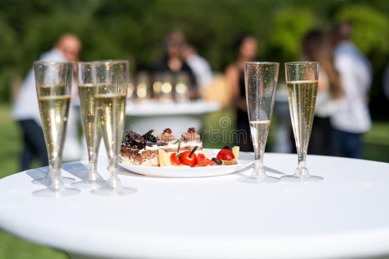 Το ευπρόσδεκτο ποτό, άποψη των γυαλιών γέμισε με τη σαμπάνια σε έναν πίνακα σε έναν κήπο στοκ εικόνα με δικαίωμα ελεύθερης χρήσης