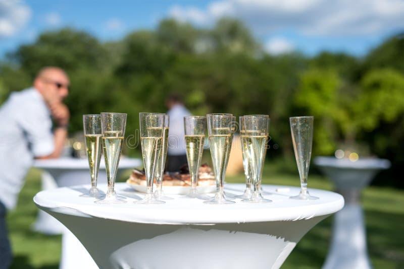 Το ευπρόσδεκτο ποτό, άποψη των γυαλιών γέμισε με τη σαμπάνια σε έναν πίνακα σε έναν κήπο στοκ εικόνες