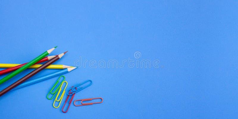 Το ευρύ έμβλημα του γραφείου χαρτικών παρέχει τις έννοιες, τα ζωηρόχρωμους μολύβια και τους συνδετήρες στο μπλε υπόβαθρο στοκ εικόνες