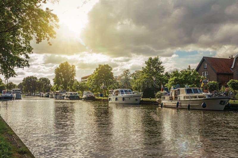 Το ευρύ δενδρώδες κανάλι με τα σπίτια και η βάρκα έδεσαν στην τράπεζά του στο ηλιοβασίλεμα σε Weesp στοκ εικόνα