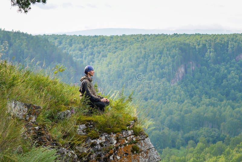 Το ευτυχές άτομο με κλειστή τη μάτια συνεδρίαση στην άκρη ενός απότομου βράχου που στη γιόγκα θέτει, χαλαρώνει και ελεύθερος χρόν στοκ εικόνα
