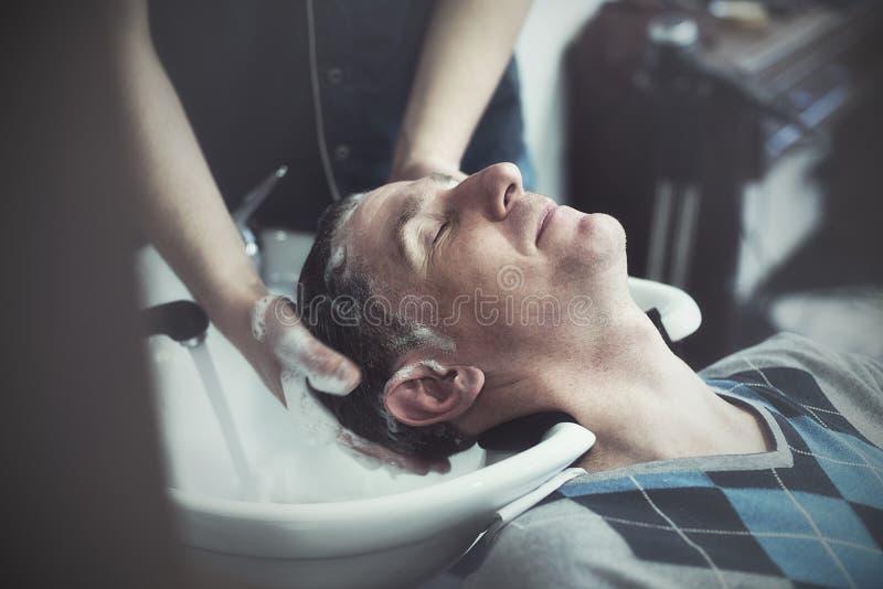 Το ευτυχές άτομο σε ένα barbershop απολαμβάνει τη διαδικασία το κεφάλι του στοκ εικόνα