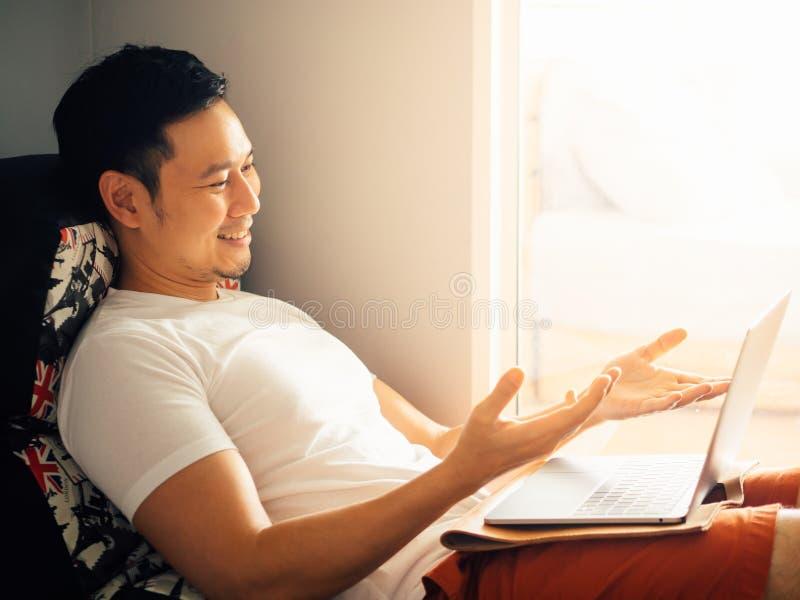 Το ευτυχές άτομο χρησιμοποιεί το lap-top και χαλαρώνει στον καναπέ το πρω στοκ εικόνα
