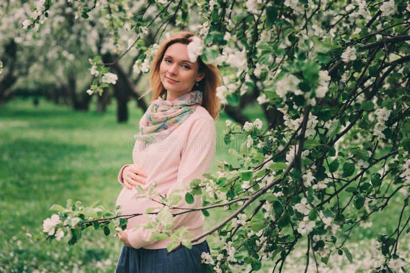 Το ευτυχές έγκυο ξανθό όμορφο περπάτημα γυναικών υπαίθριο την άνοιξη σταθμεύει ή καλλιεργεί στοκ φωτογραφίες